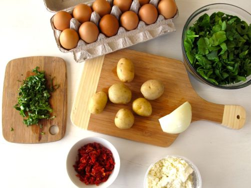 Frittata ingredients: Eggs, potatoes, spinach, sundried tomatoes, basil, and feta