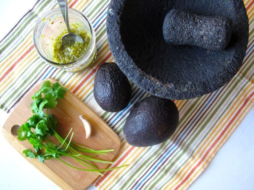 Volcanic rock molcajete, avocados, cilantro, garlic, and roasted tomatillo salsa