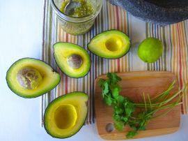 Avocados and cilantro for Roasted Tomatillo Guacamole