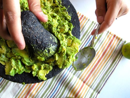 Mashing avocados in the molcajete