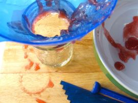Canning the rhubarb jam: hot jam gels nicely on a cool dish