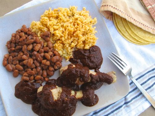 Mole Poblano with chicken, pinto beans, and Spanish rice