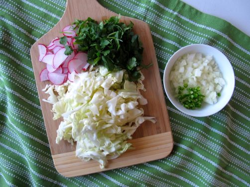 Chicken Pozole fixings: radishes, cilantro, cabbage, onion, serrano, and limes.