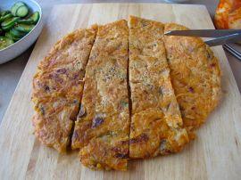 Cutting the kimchijeon (kimchi pancake)