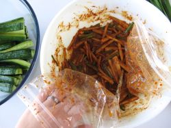 Using plastic bags as gloves to make stuffed Cucumber Kimchi (Oi Sobagi)